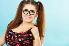 Happy teenage woman holding fake eyeglasses on stick. Happy young teenage woman holding fake eyeglasses on stick having fun. Photo and carnival funny accessories Stock Photo