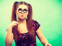 Happy teenage woman holding fake eyeglasses on stick. Happy young teenage woman holding fake eyeglasses on stick having fun. Photo and carnival funny accessories Royalty Free Stock Photos