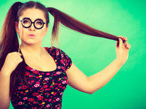 Happy teenage woman holding fake eyeglasses on stick. Happy young teenage woman holding fake eyeglasses on stick having fun. Photo and carnival funny accessories Royalty Free Stock Photo