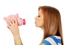 Happy teenage woman kissing a piggybank Royalty Free Stock Image