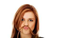 Happy teenage woman making moustache from hair Royalty Free Stock Images