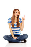 Happy teenage woman pointing for something Stock Images