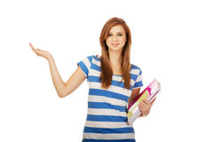 Happy teenage woman presenting something on open palm.  royalty free stock photography
