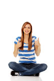 Happy teenage woman sitting with cross legged Royalty Free Stock Image