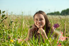 Happy  teenager. Girl lying in meadow grass Royalty Free Stock Photo