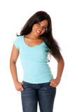 Happy teenager. Beautiful happy smiling African Caribbean teenager standing with thumbs in pocket wearing blue shirt and jeans, isolated Stock Photos