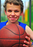 Happy teenager with a basketball. Portrait of a happy teenager with a basketball Royalty Free Stock Photos