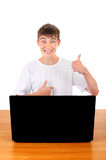 Happy Teenager behind Laptop. Happy Teenager with Badge on t-shirt at the Desk with Laptop Isolated on the White Royalty Free Stock Photos