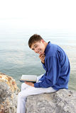 Happy teenager with book. Happy teenager sitting with a book on the stone on the seaside Stock Photo