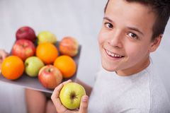 Happy teenager boy holding a plate of fresh fruits royalty free stock image