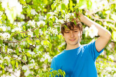 Happy teenager boy holds branch with white flowers Stock Images