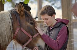 Happy teenager boy with horse. At ranch Stock Photos