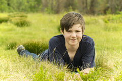 Happy teenager boy. A happy teenager boy lying in grass Stock Images