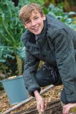 Happy Teenager Boy Male Young Adult Gardening. Happy smiling male boy child teenager young adult gardening with bucket and garden fork in a vegetable patch Stock Photos