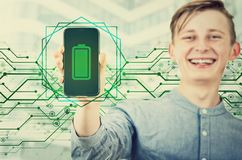 Free Happy Teenager Boy Showing His Smartphone With The Full, Green Battery Bar On The Screen. Joyful Adolescent Guy Presenting A New Royalty Free Stock Images - 160529779