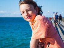 Happy boy on a pier at baltic sea stock images