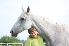 Happy teenager boy and white horse at the field Stock Image