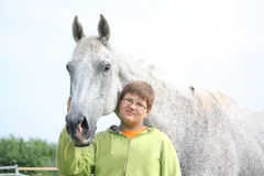 Happy teenager boy and white horse at the field Stock Photos
