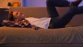 Happy teenager coming home from school, lying on sofa and relaxing, leisure time stock video