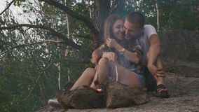 Happy teenager couple friying sausages on smoky bonfire in the forest. Young man happily kisses his girlfriend stock video