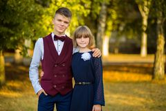 Happy teenager couple of high school students in festive school uniform on background autumn park. Beginning of lessons. Back to school. Older brother and stock image
