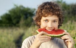 Happy teenager eating watermelon. In the garden stock photography