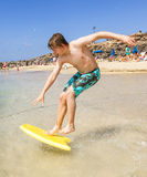 Happy teenager enjoys surfing in the waves. Happy boy enjoys surfing in the waves at the beach stock photography