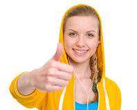 Happy teenager girl in earphones showing thumbs up Stock Photos