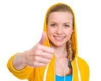 Happy teenager girl in earphones showing thumbs up Stock Photos