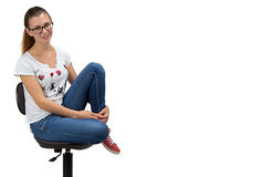 Happy teenager girl with glasses sitting on chair Stock Images