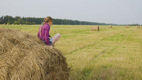 Happy teenager girl on hay stack at farming field. Smiling girl showing thumbs up on countryside field. Hay straw on stock video footage