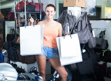 Happy teenager girl holding shopping bags in boutique Royalty Free Stock Images
