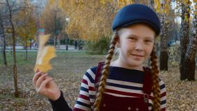 Happy teenager girl holding yellow maple leaf in hand near face. Portrait playful girl with autumn foliage park. Face stock video footage