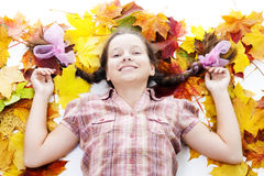 Happy teenager girl lay in maple leafs. On white background Stock Photo
