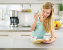 Happy teenager girl reading book and eating yogurt. In kitchen Royalty Free Stock Photography
