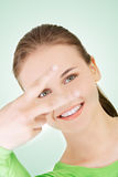 Happy teenager girl showing victory sign Stock Photography