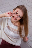 Happy teenager girl smiling and showing victory sign Stock Photos