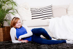 Happy teenager girl smiling sitting on couch Royalty Free Stock Images