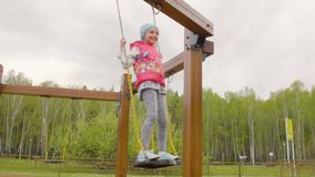 Happy teenager girl on swing in spring city park, low angle view. Slow motion stock footage