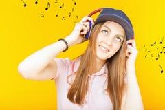 Happy teenager girl uses a headphones stock photos