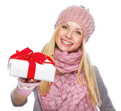 Happy teenager girl in winter hat giving presenting box Royalty Free Stock Images
