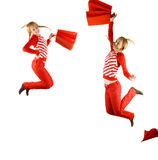 Happy teenager girls. With red bags  jumping - over white Royalty Free Stock Photo