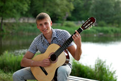 Happy teenager with a guitar by the river. Happy young man holding a guitar by the river royalty free stock images