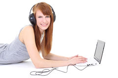 Happy teenager with headphones and laptop Stock Photography