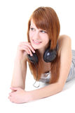 Happy teenager with headphones lying Stock Photography