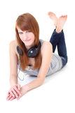 Happy teenager with headphones lying Stock Images