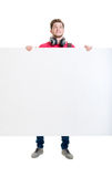 Happy teenager holding a blank banner isolated on white.  Royalty Free Stock Image