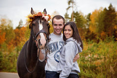 Happy teenager hugging couple with a horse Royalty Free Stock Images