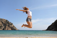 Happy teenager jumping on the beach Stock Image