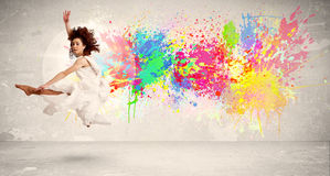 Happy teenager jumping with colorful ink splatter on urban backg Stock Photos